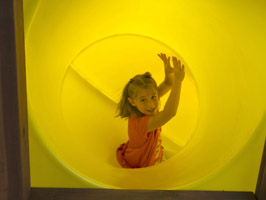 girl sliding down spiral tube slide
