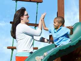 mom high fiving kid on slide